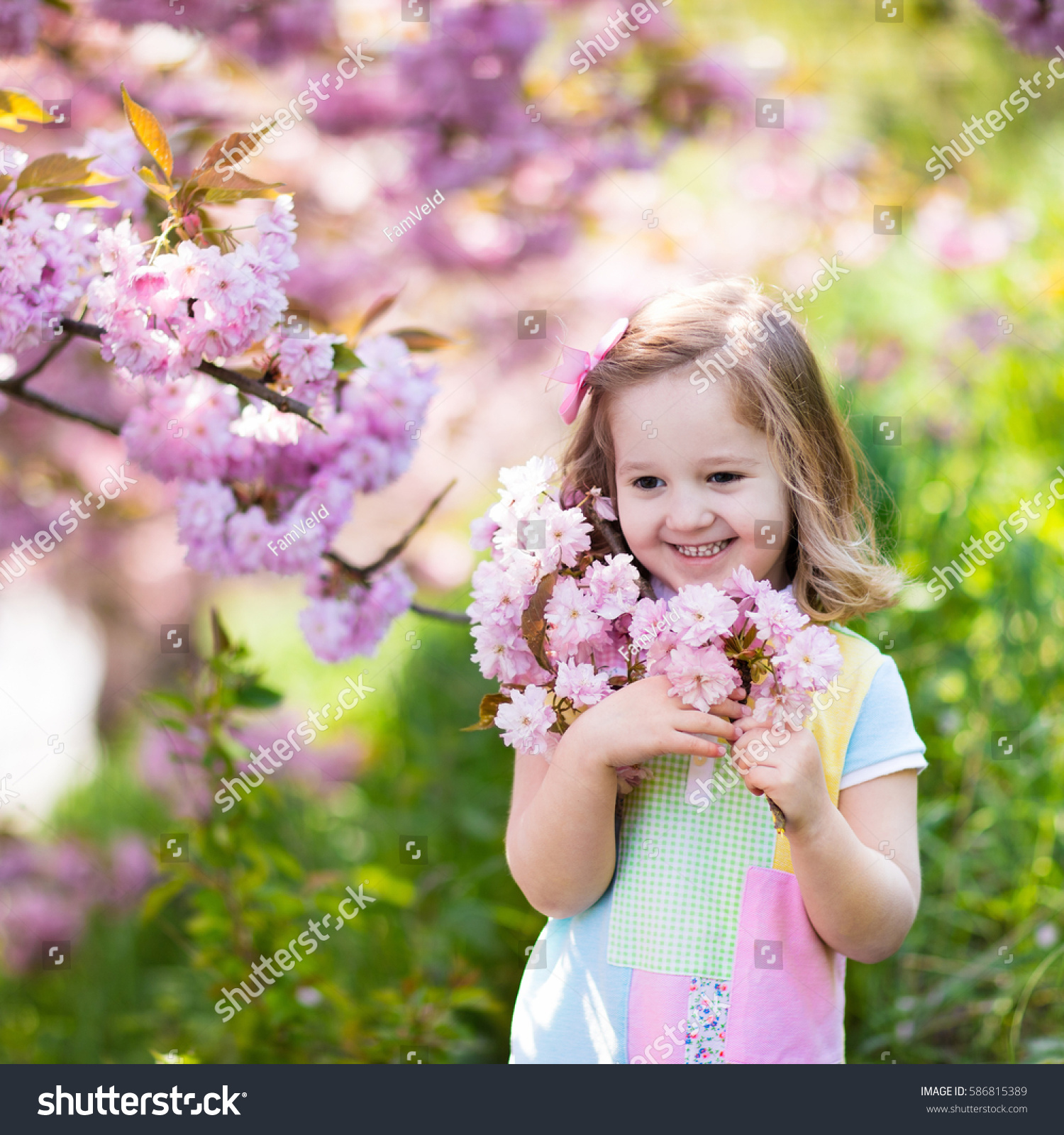 Little Happy Girl Playing Under Blooming Cherry Tree With Pink