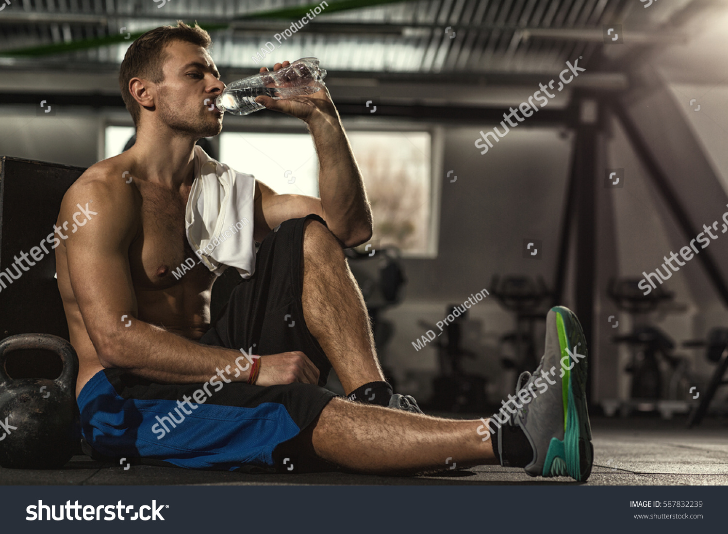 Drink water shirtless sportsman resting after stock photo drink water shirtless sportsman resting after training at the gym sitting on the floor drinking sciox Gallery