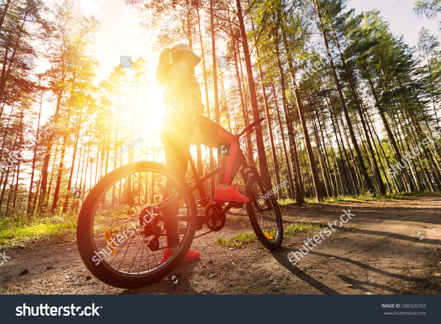 Woman Riding Mountain Bicycle Along Path Stock Photo