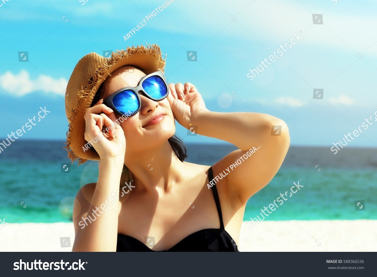 Young female fashion model smiling and wearing big sunglasses on a beach, sun protection and skincare concept. #588366536
