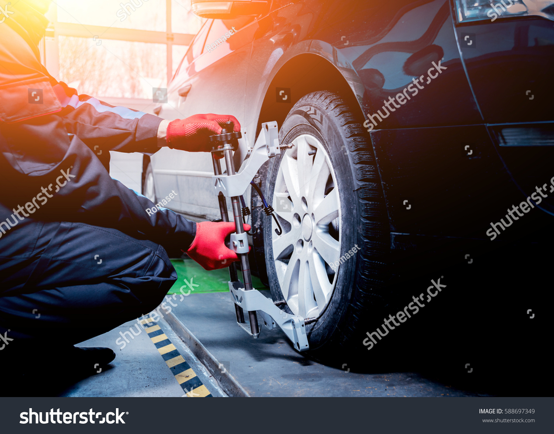 Car mechanic installing sensor during suspension adjustment. Wheel alignment work at repair service station #588697349