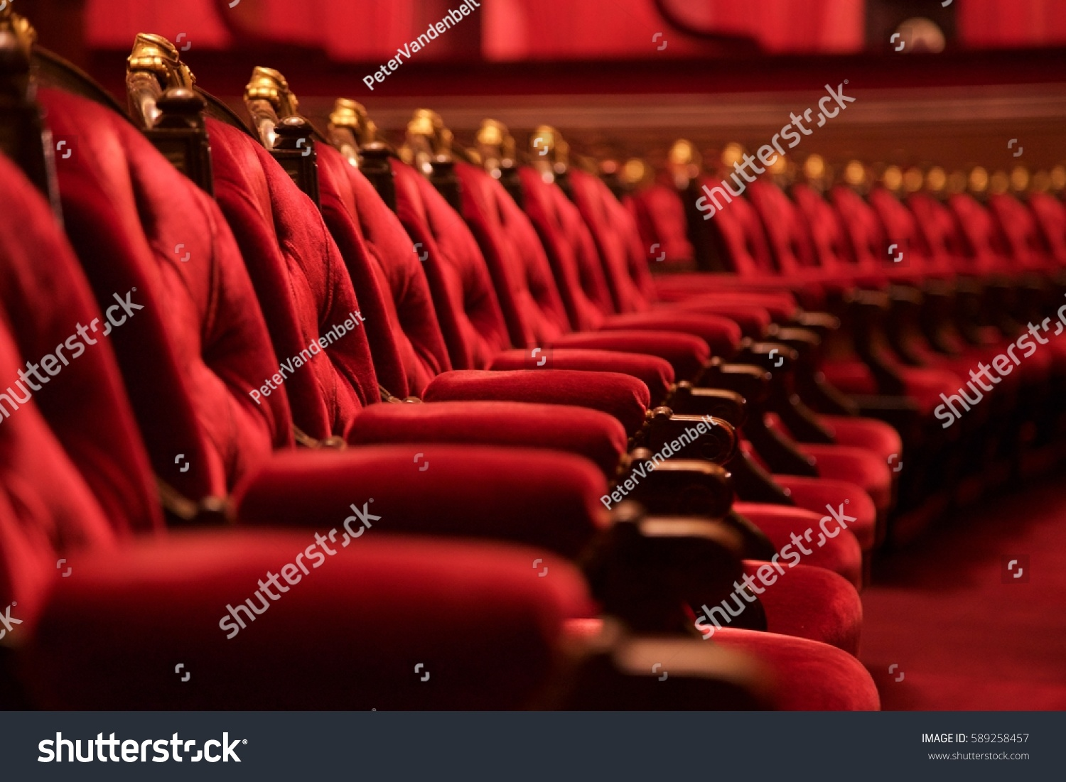 Traditional classically regal ornate rounded wood armed formal plush deep red velvet opera movie theater chairs in curved row with decorative gold molding in fancy carpeted venue #589258457
