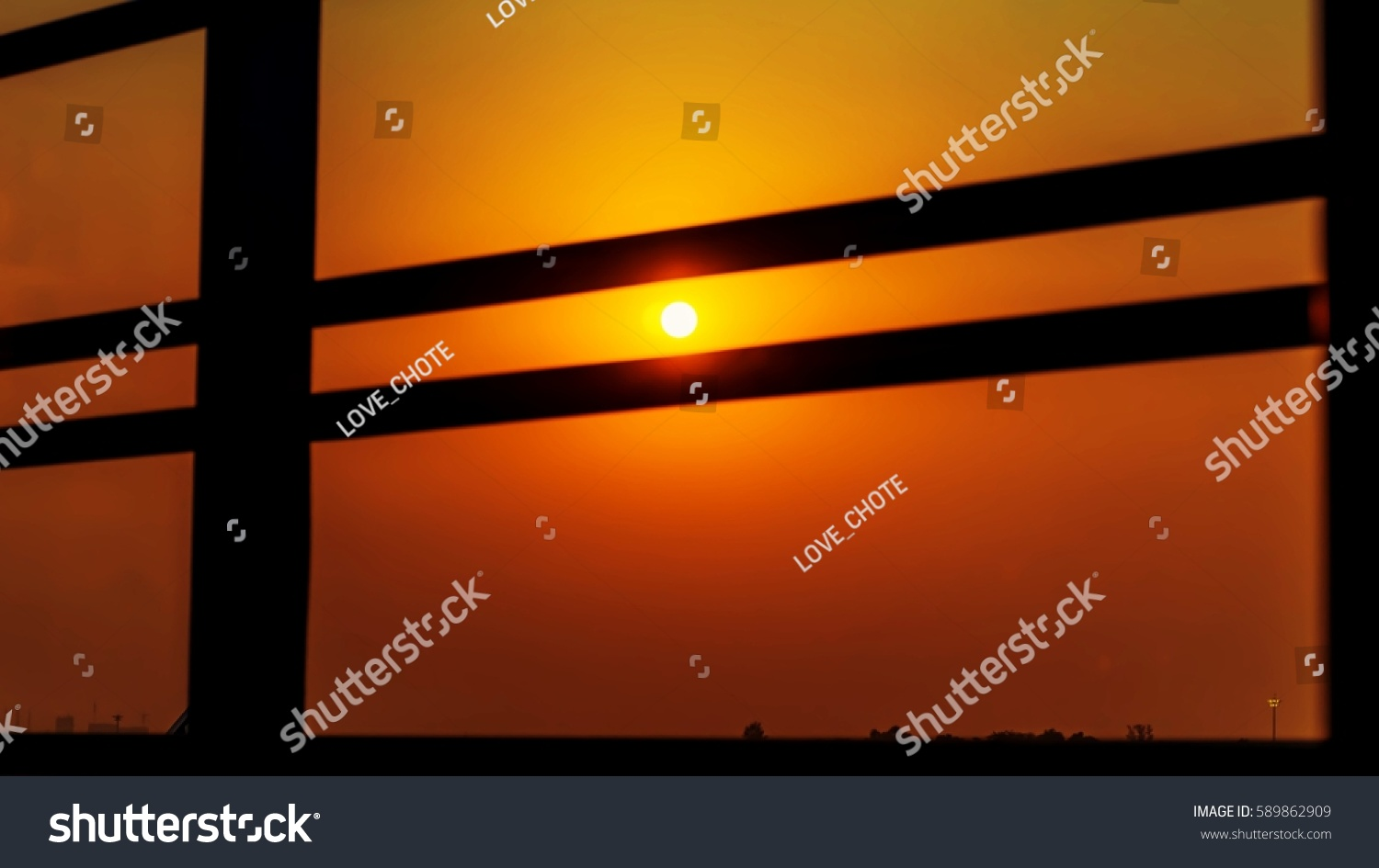 Beautiful sunset landscape in town, yellow and orange sky above it with sun golden . Amazing summer sunset view  #589862909