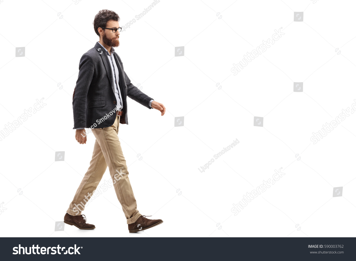 Full length profile shot of a young bearded man walking isolated on white background