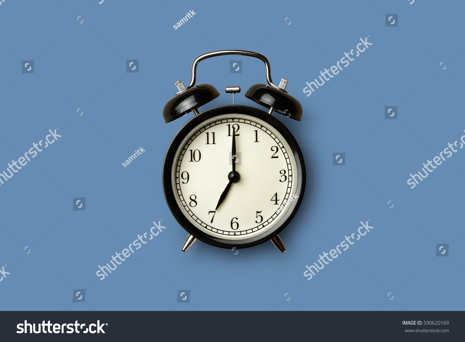 black vintage alarm clock on blue color background