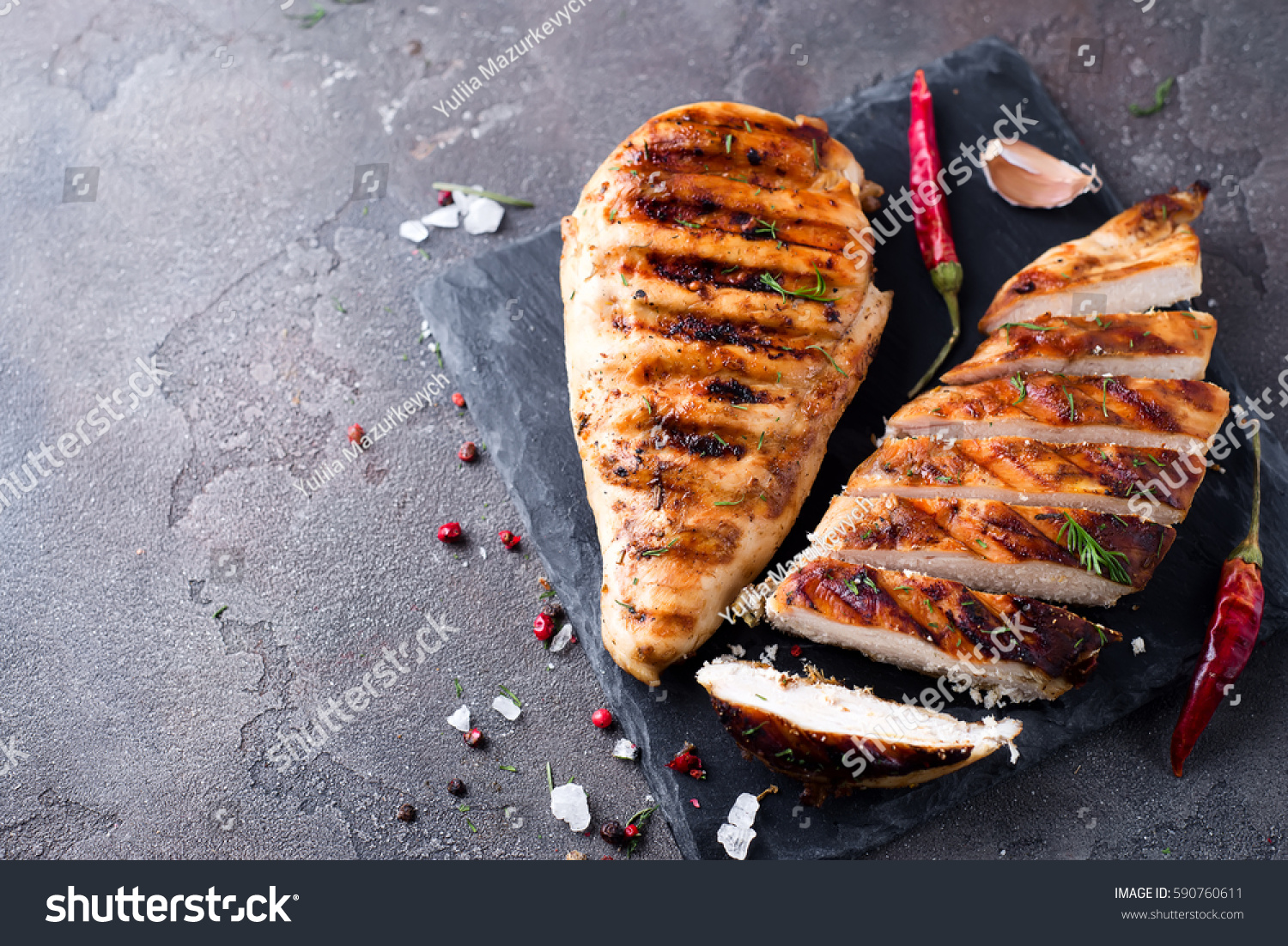 whole and sliced chicken breast with spices on a stone board, top view copy space #590760611