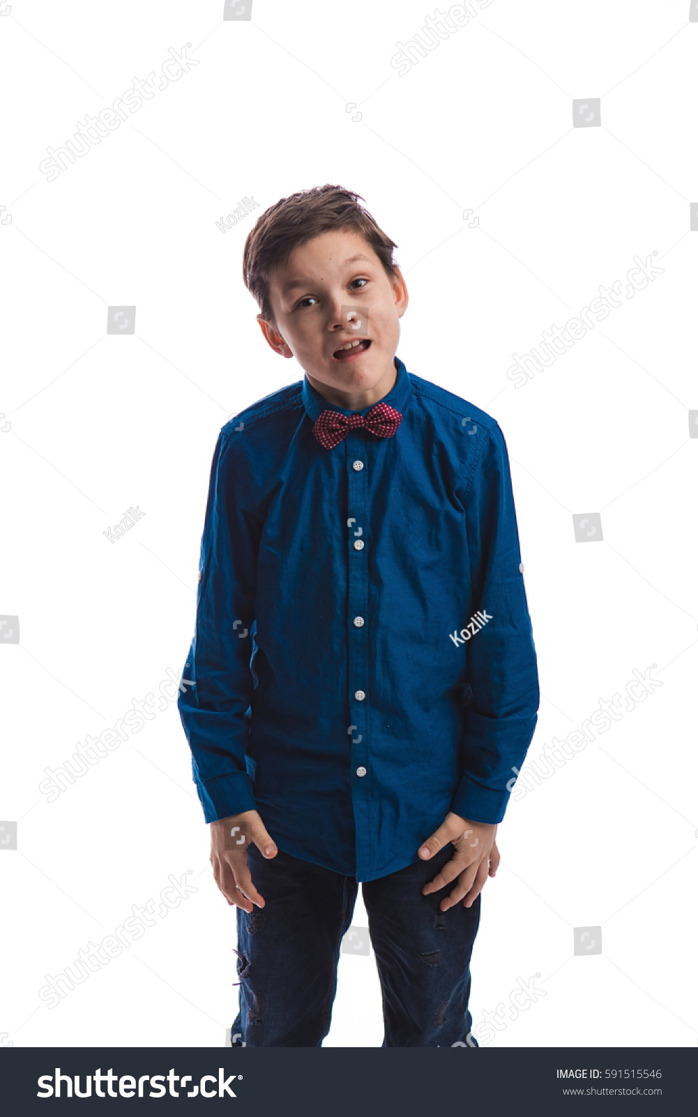 Boy Brunette In A Blue Shirt With A Red Tie Is Posing In The Studio