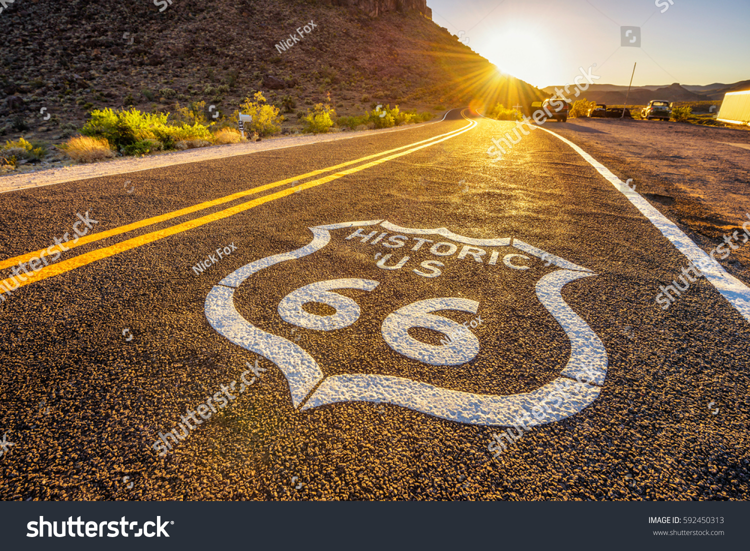 Street sign on historic route 66 in the Mojave desert photographed against the sun at sunset #592450313