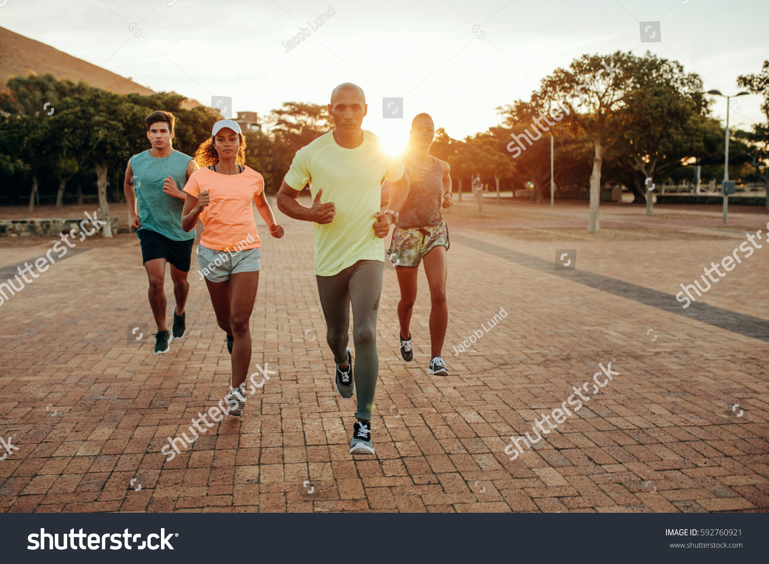 Portrait of young runners on path at the park. Group running outdoors in evening. #592760921