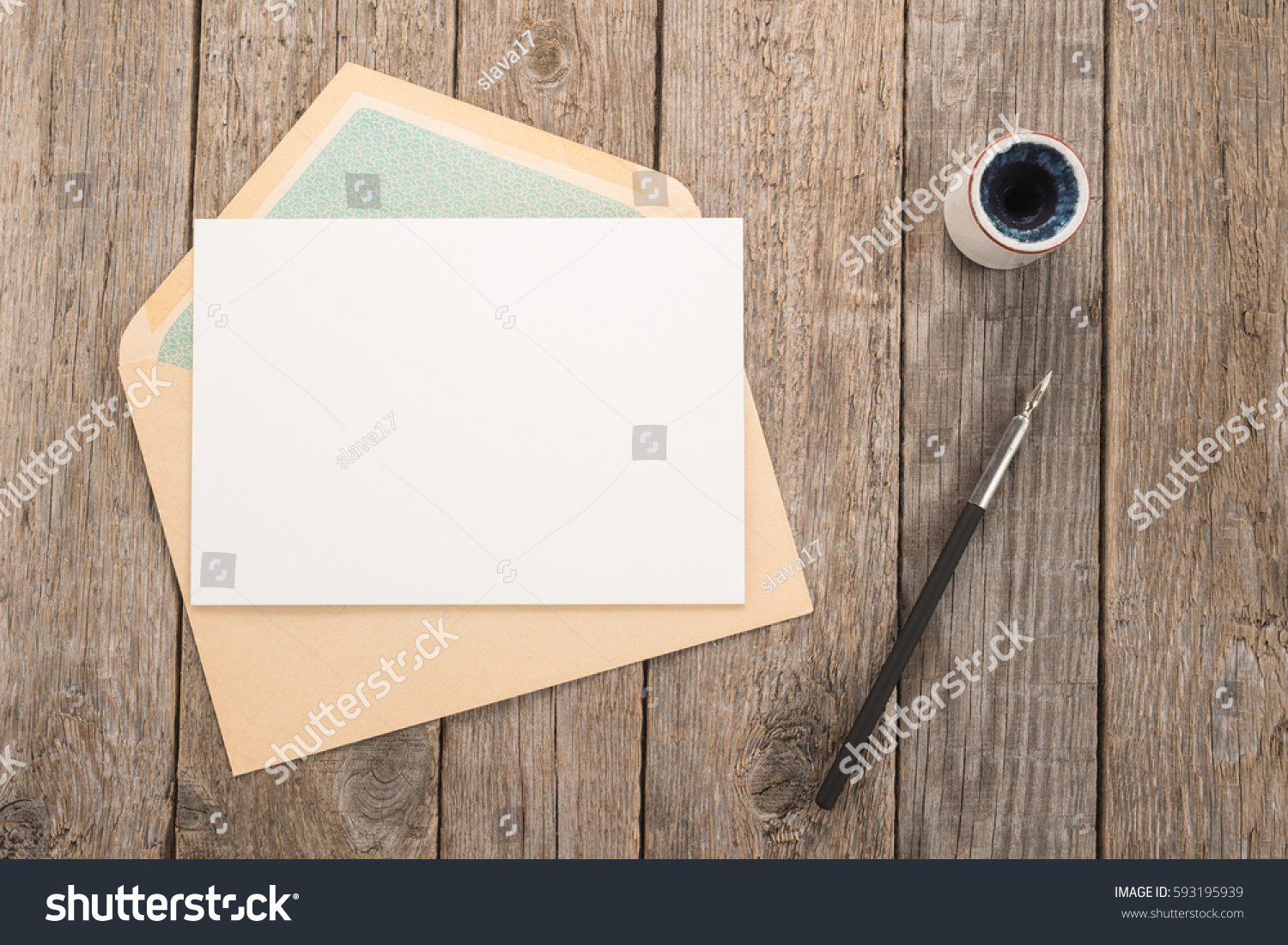 Envelope, ink pen, inkwell on a wood table #593195939
