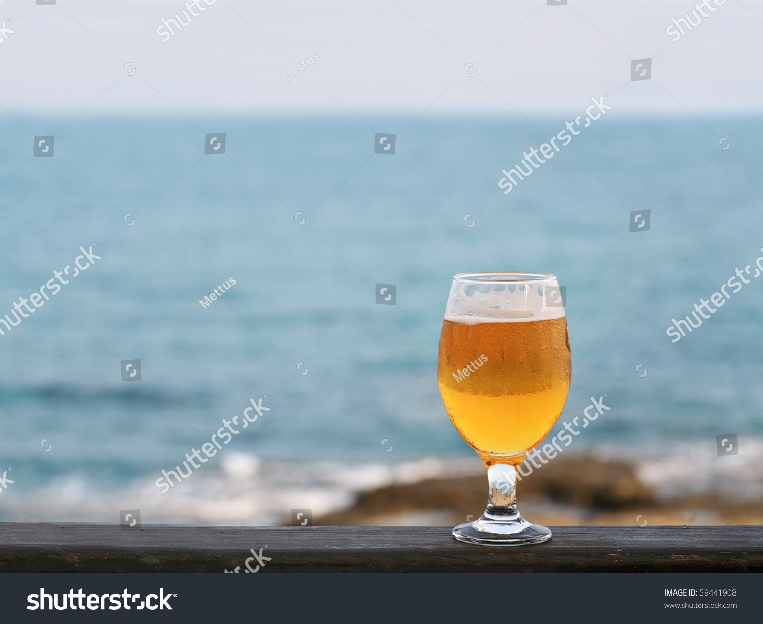 One glass of beer against sea and coastline a lot of space for text. Glas of beer on wooden fence of beach bar. Copy-space. Relaxation Concept. A Lot of Space for Text.