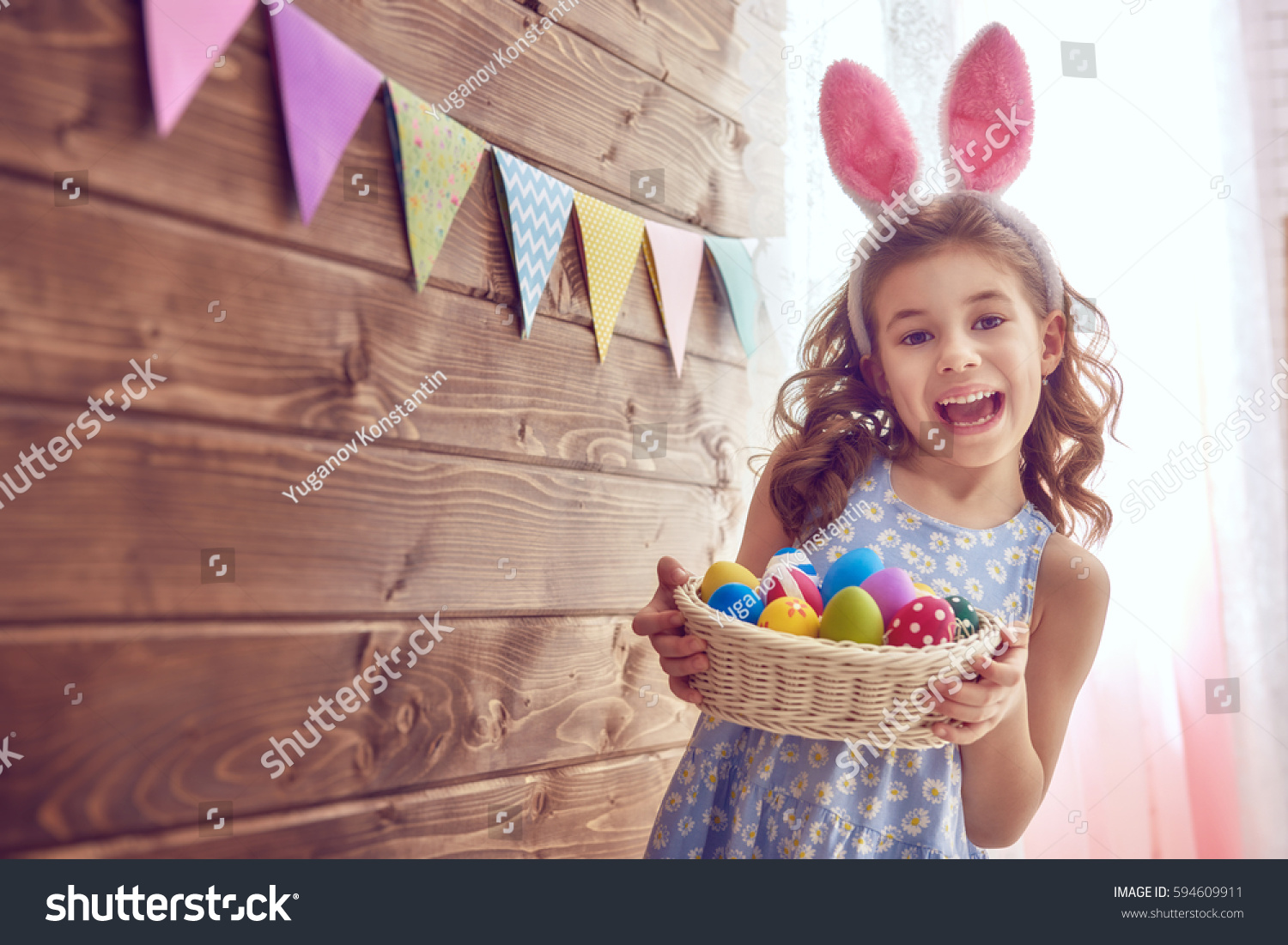 Cute little child wearing bunny ears on Easter day. Girl holding basket with painted eggs. #594609911