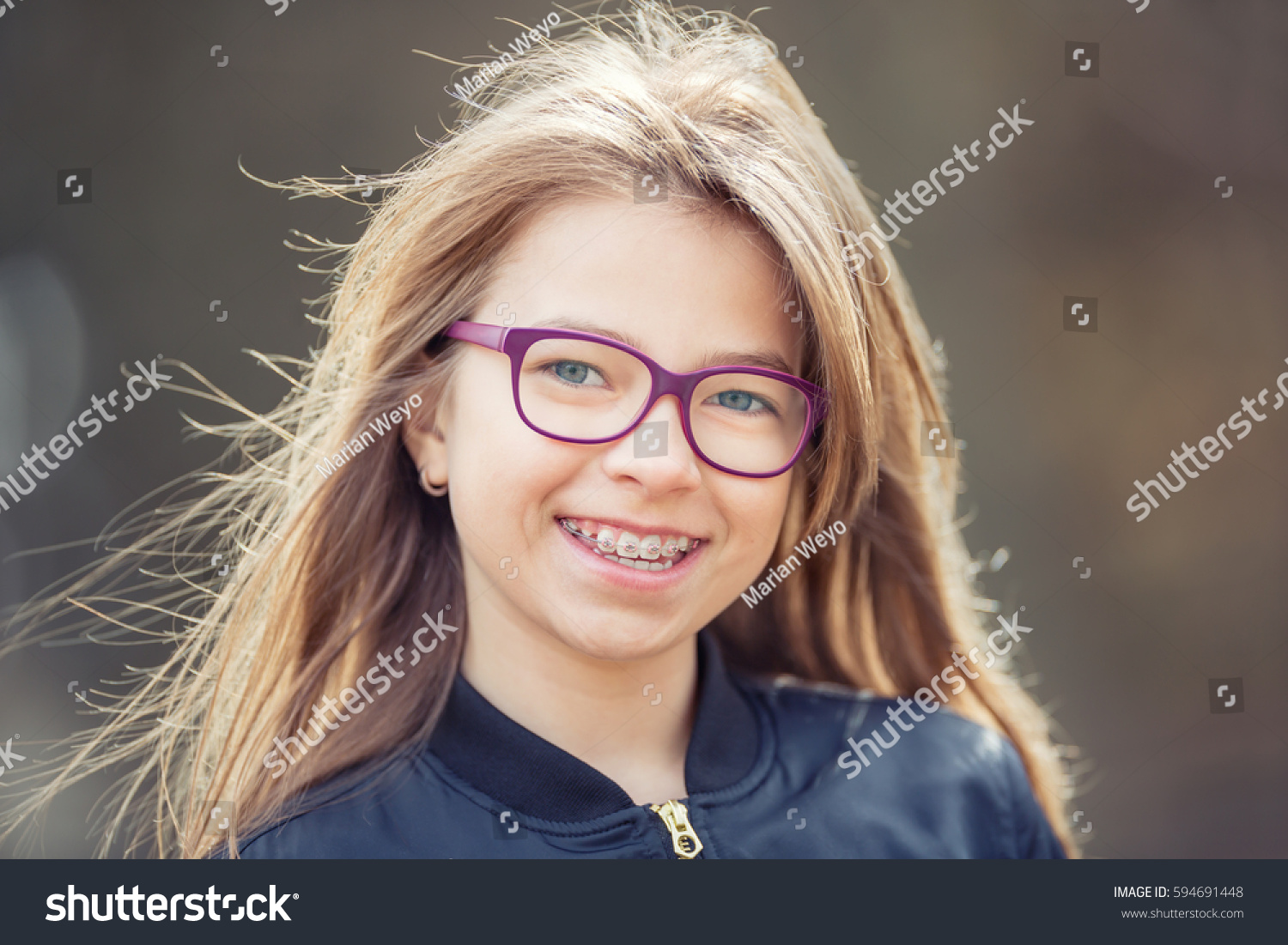 6d3fe21eff16 Portrait of a beautiful smiling young girl with dental braces and glasses.