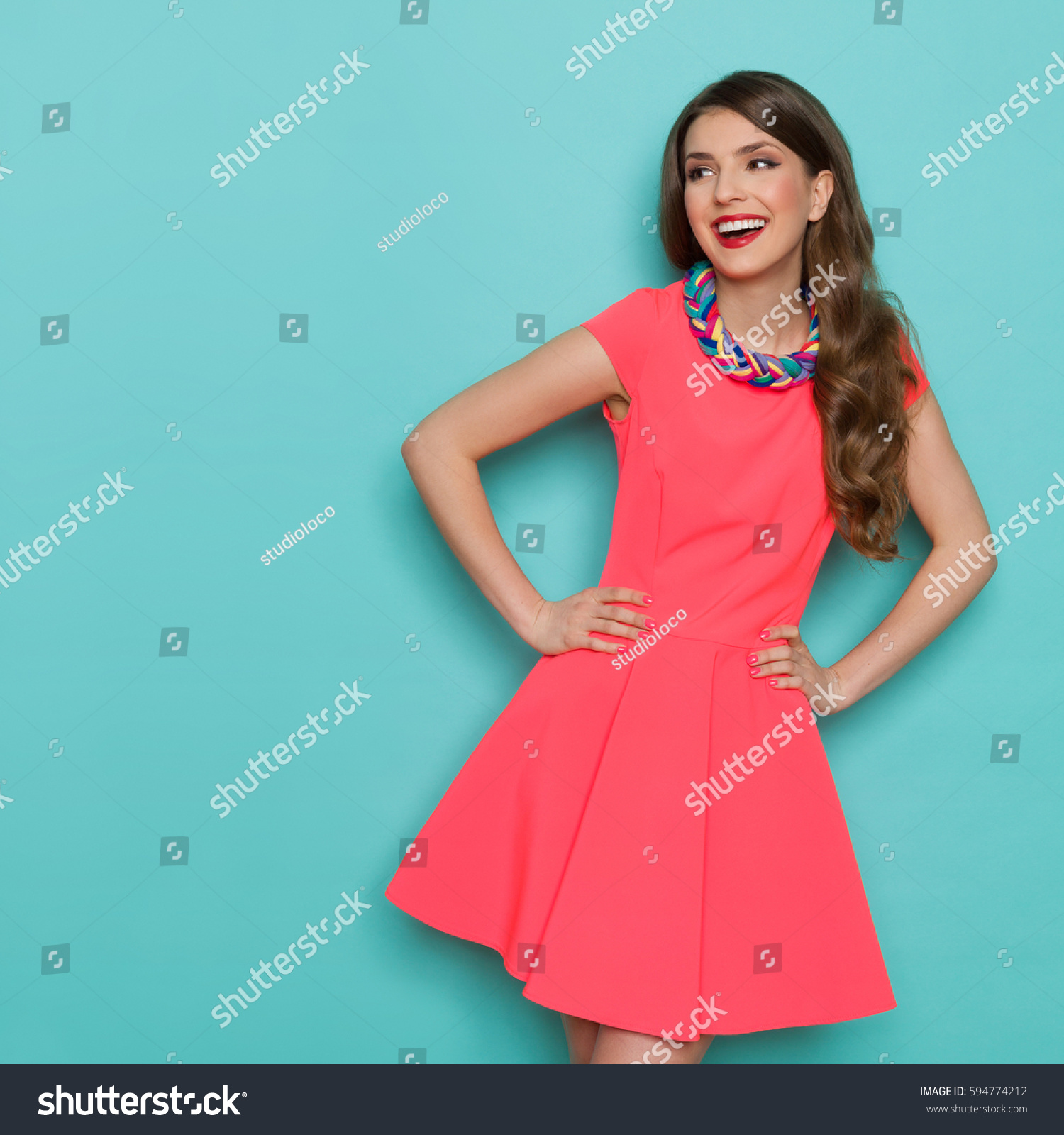 Amused beautiful young woman in pink mini dress posing with hand on hip and looking away. Three quarter length studio shot on turquoise background. #594774212