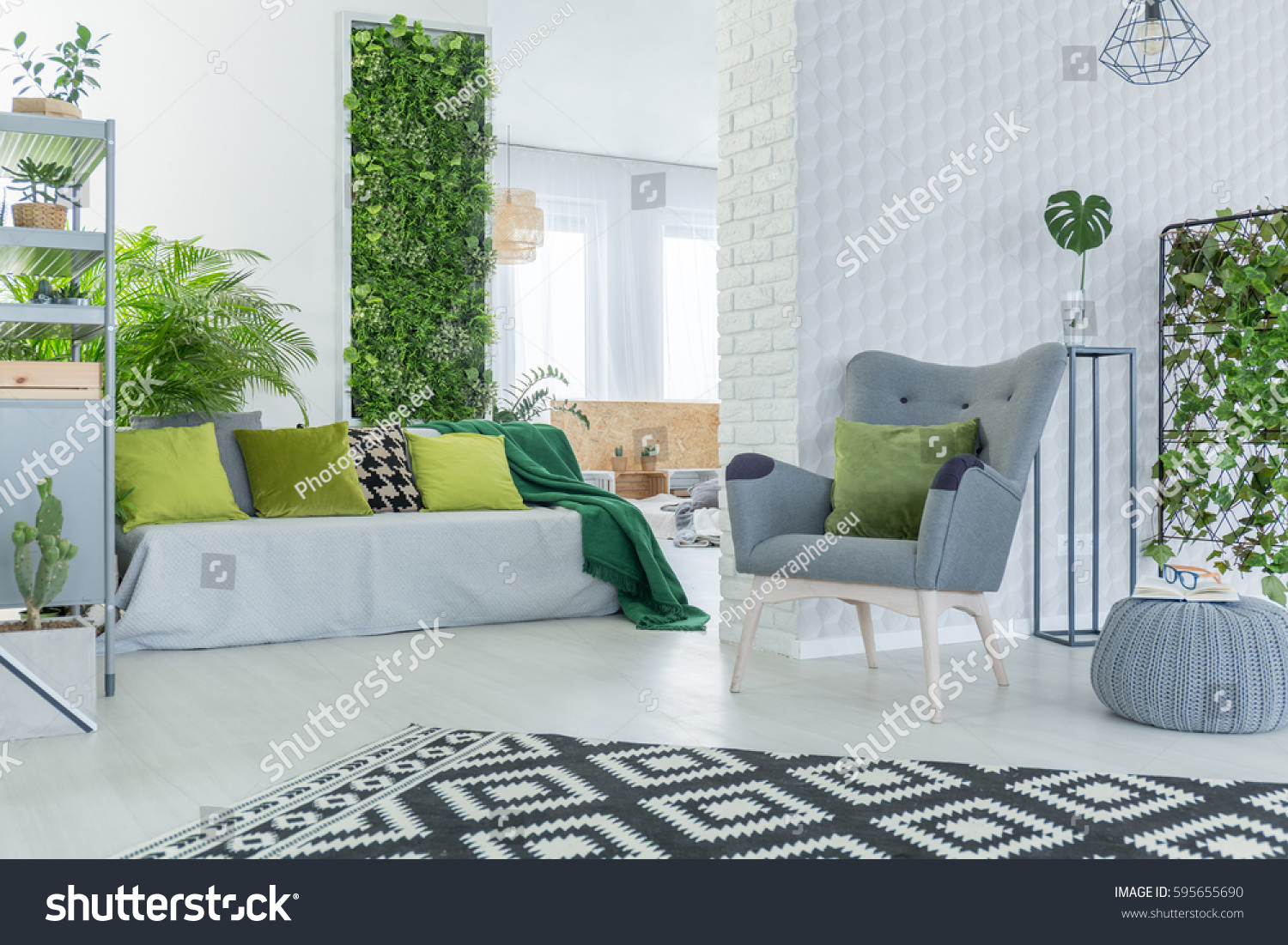 Bright Living Room With Sofa Armchair Pouf And Green Plants