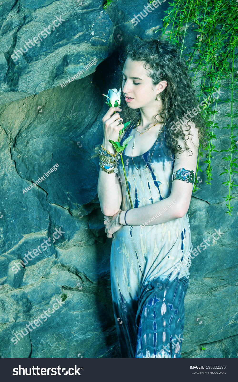 37b13f8a268 American teenager girl with curly hair, wearing patterned long dress,  bracelet, standing against.