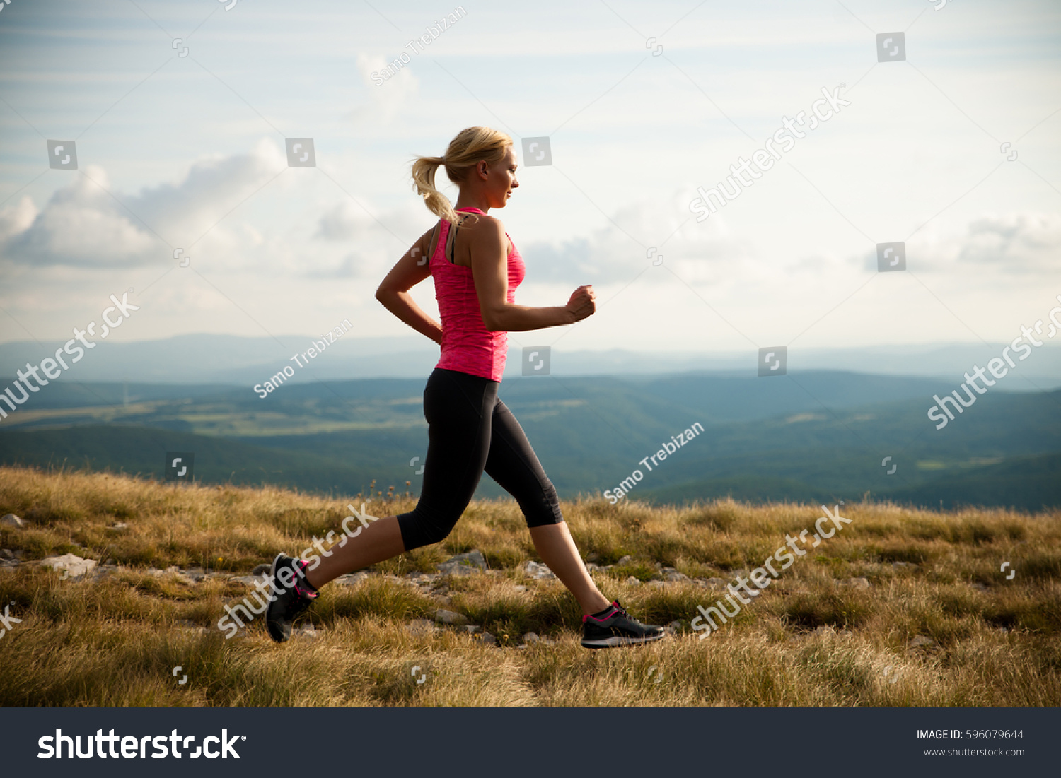 runner - woman runs cross country on a path in early autumn #596079644