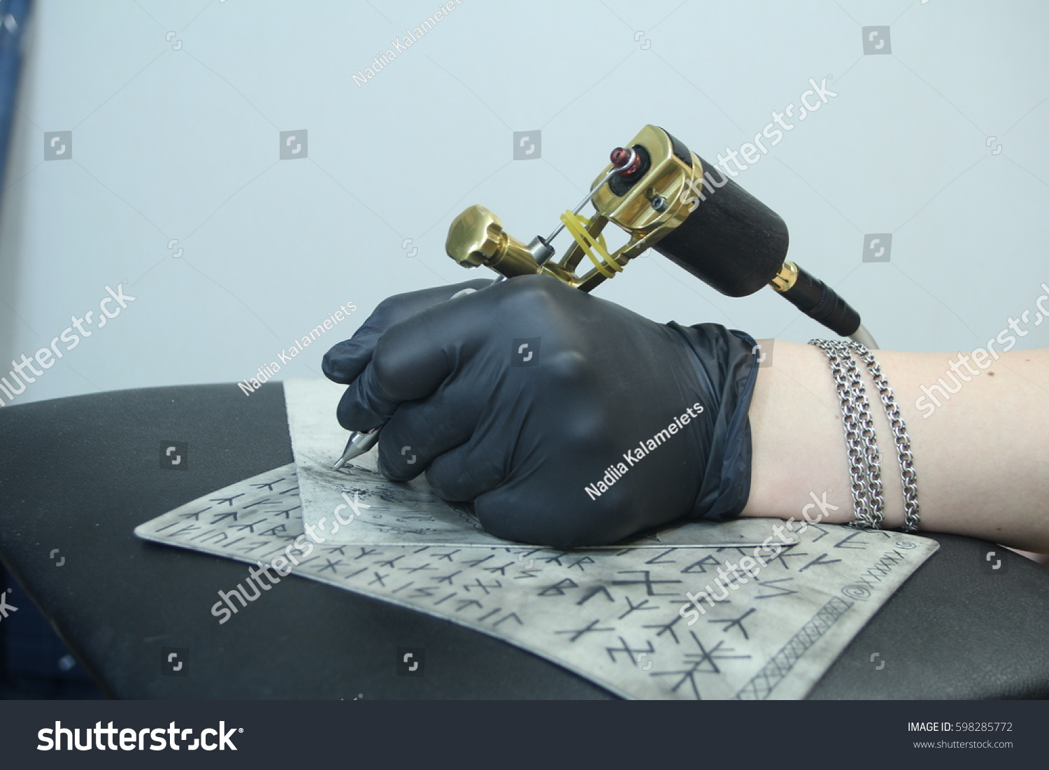 Hand tattoo artist holding tattoo machine stock photo for Process of tattooing