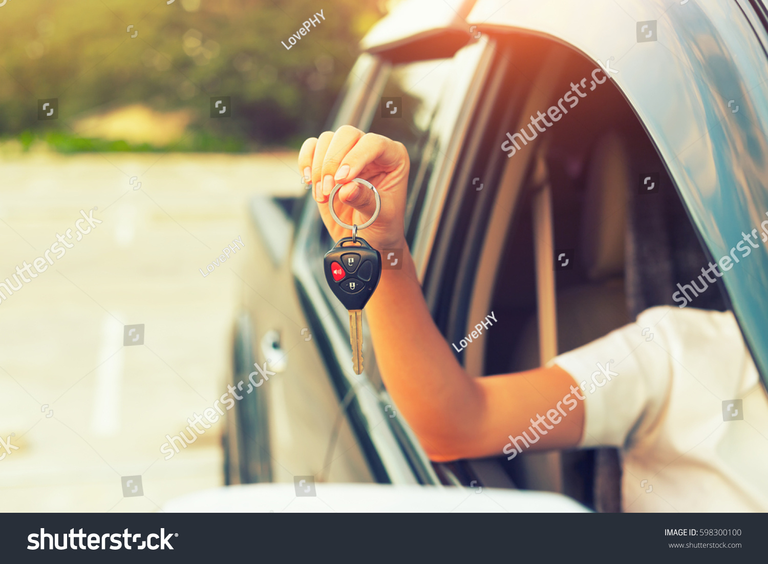 Used car and dealership concept. By woman's hand holding or giving a car key. Also for used car for sale concept, first car buy or purchase, sell, driver license, hire, loan, insurance and auction etc #598300100