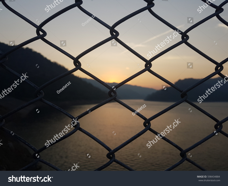 Metal mesh wire fence blur mountain stock photo