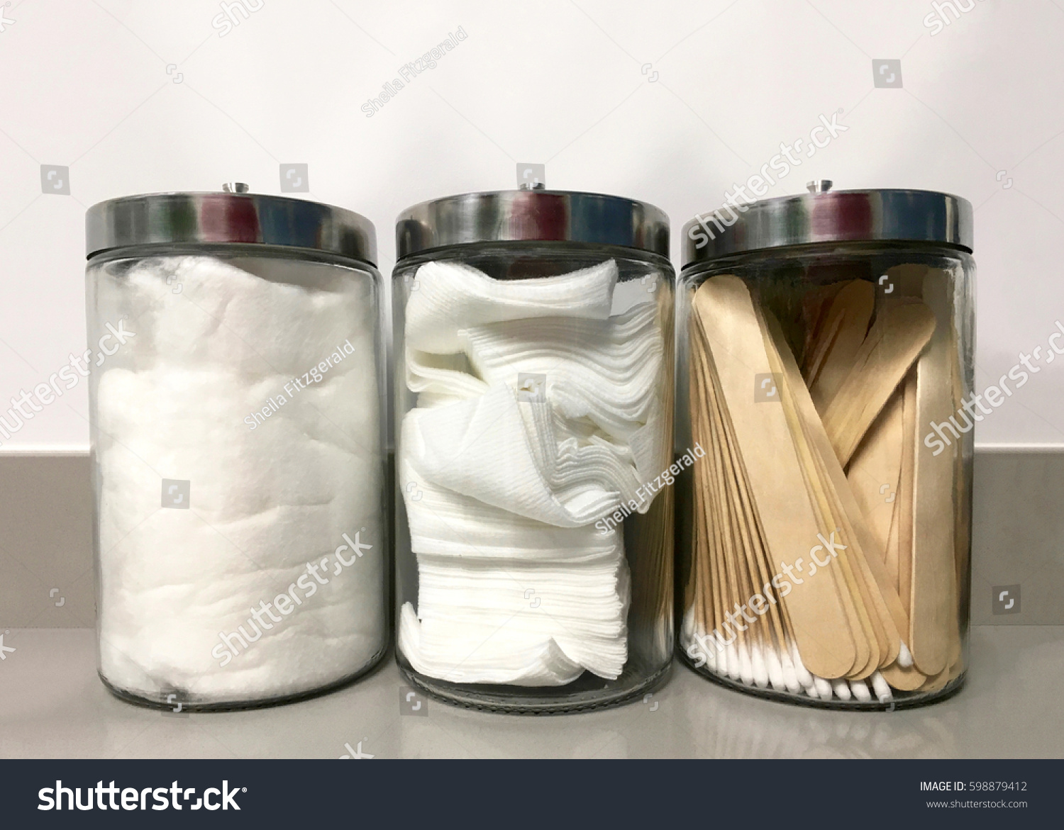 Three glass jars on medical office counter with non-sterile q-tips, tongue