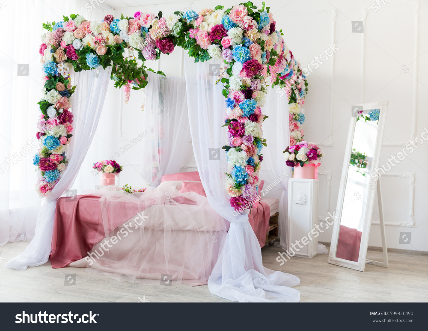 Bed Decorated With Flowers In Light Bedroom.