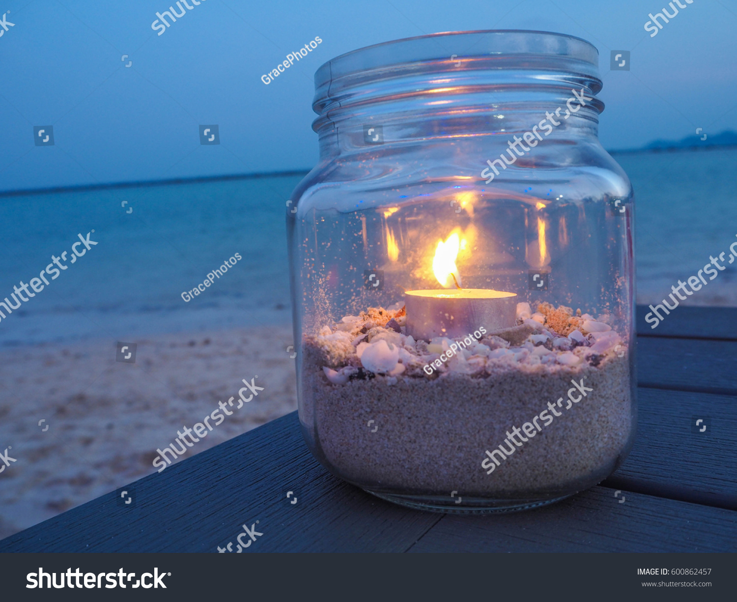 A clear bottle fill in of candle light and sand with seashell a decoration of some & Clear Bottle Fill Candle Light Sand Stock Photo (100% Legal ...