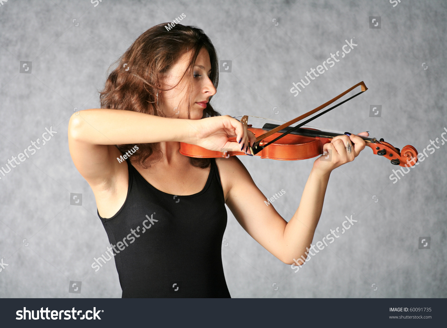 Beautiful brown haired girl with violin on grey background. Woman artist with violin in music concept on stage.