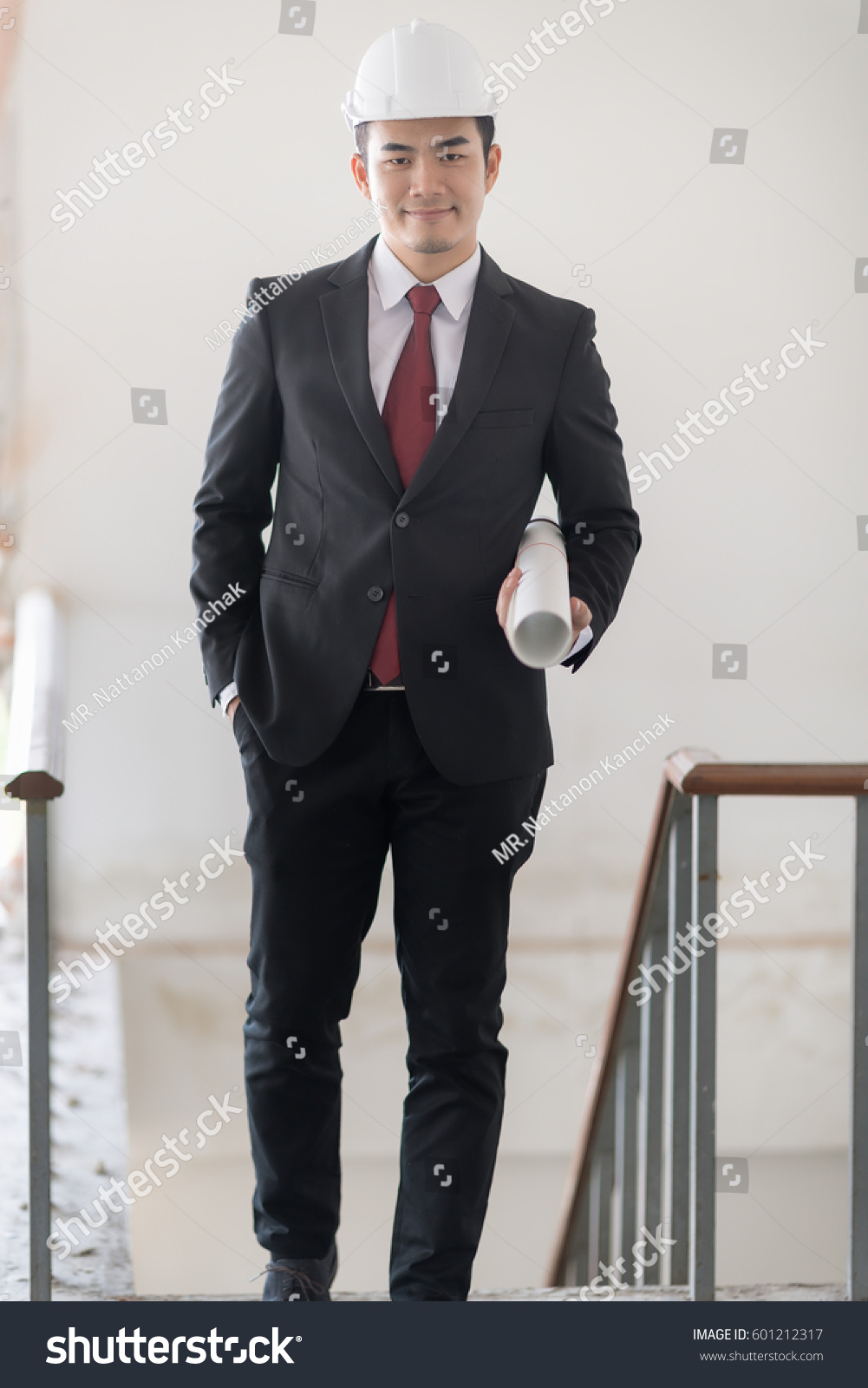 57c935c3db75 Business man in white helmet with black suit and red necktie is walking on  the staircase.