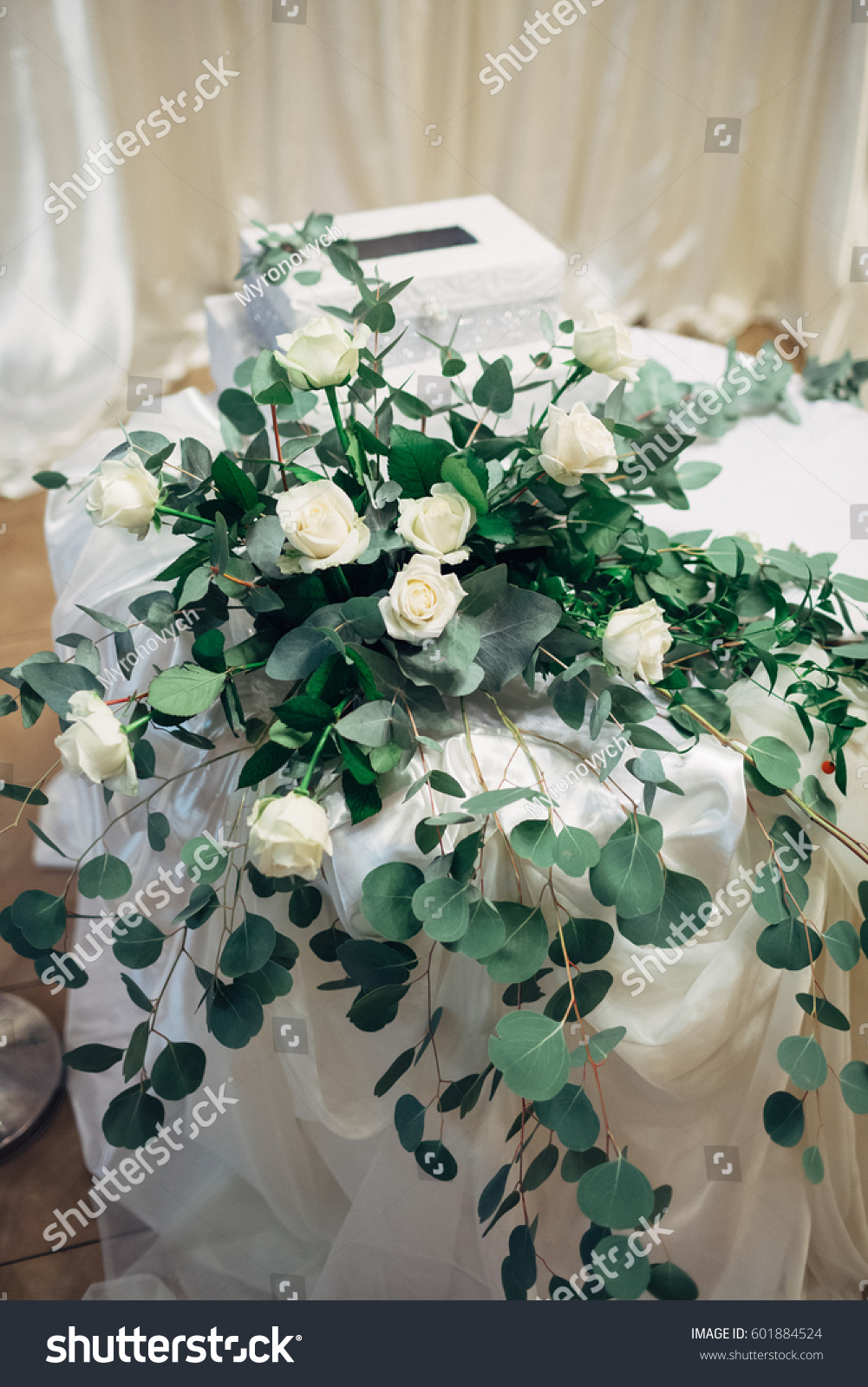 Bouquet Of White Roses And Long Green Branches Stands On Little