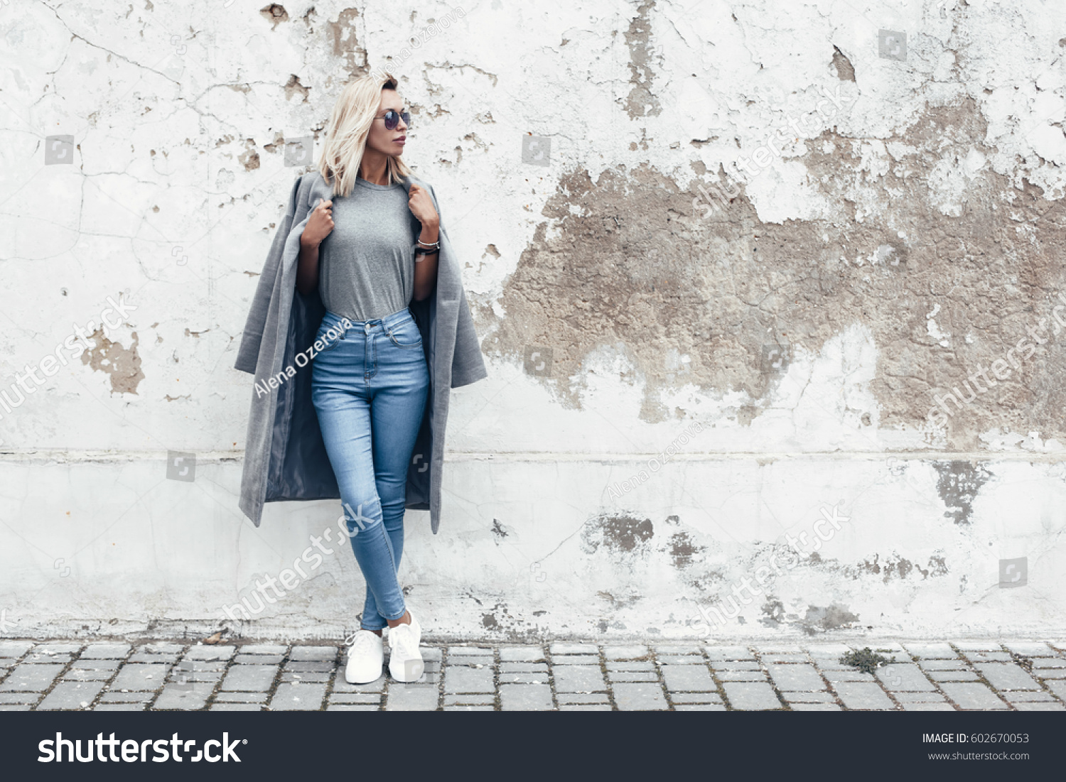 Hipster girl wearing blank gray t-shirt, jeans and coat posing against rough street wall, minimalist urban clothing style, mockup for tshirt print store