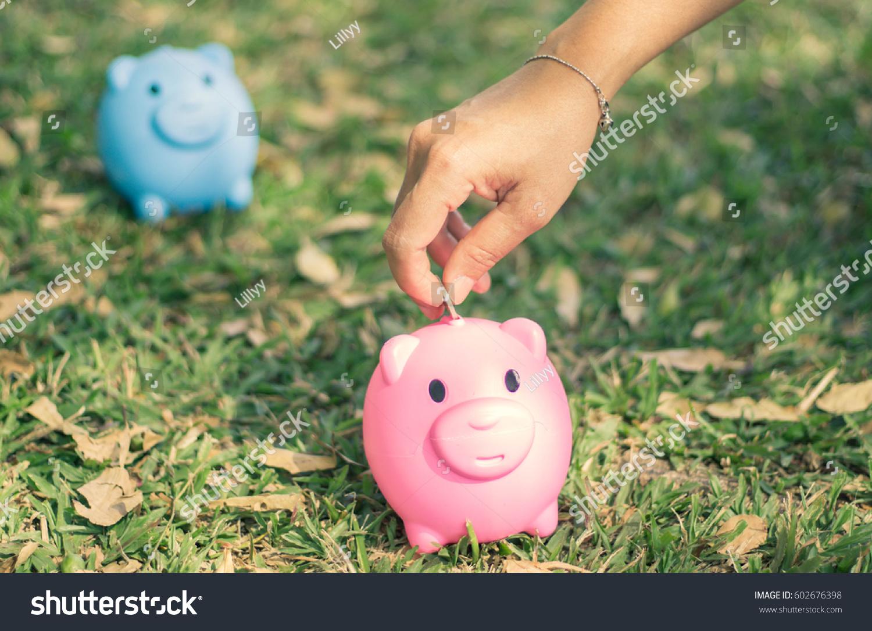saving hand putting coin into piggy stock photo 602676398