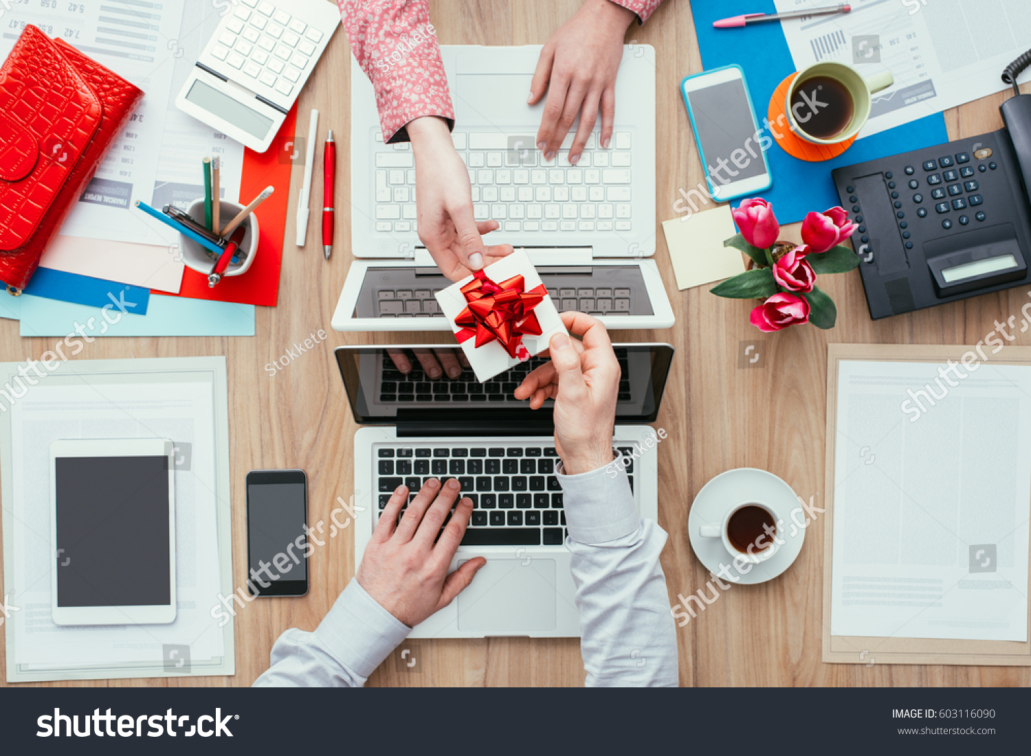 Woman Receiving A Beautiful Gift From Her Male Colleague While Working In  The Office; Relationships