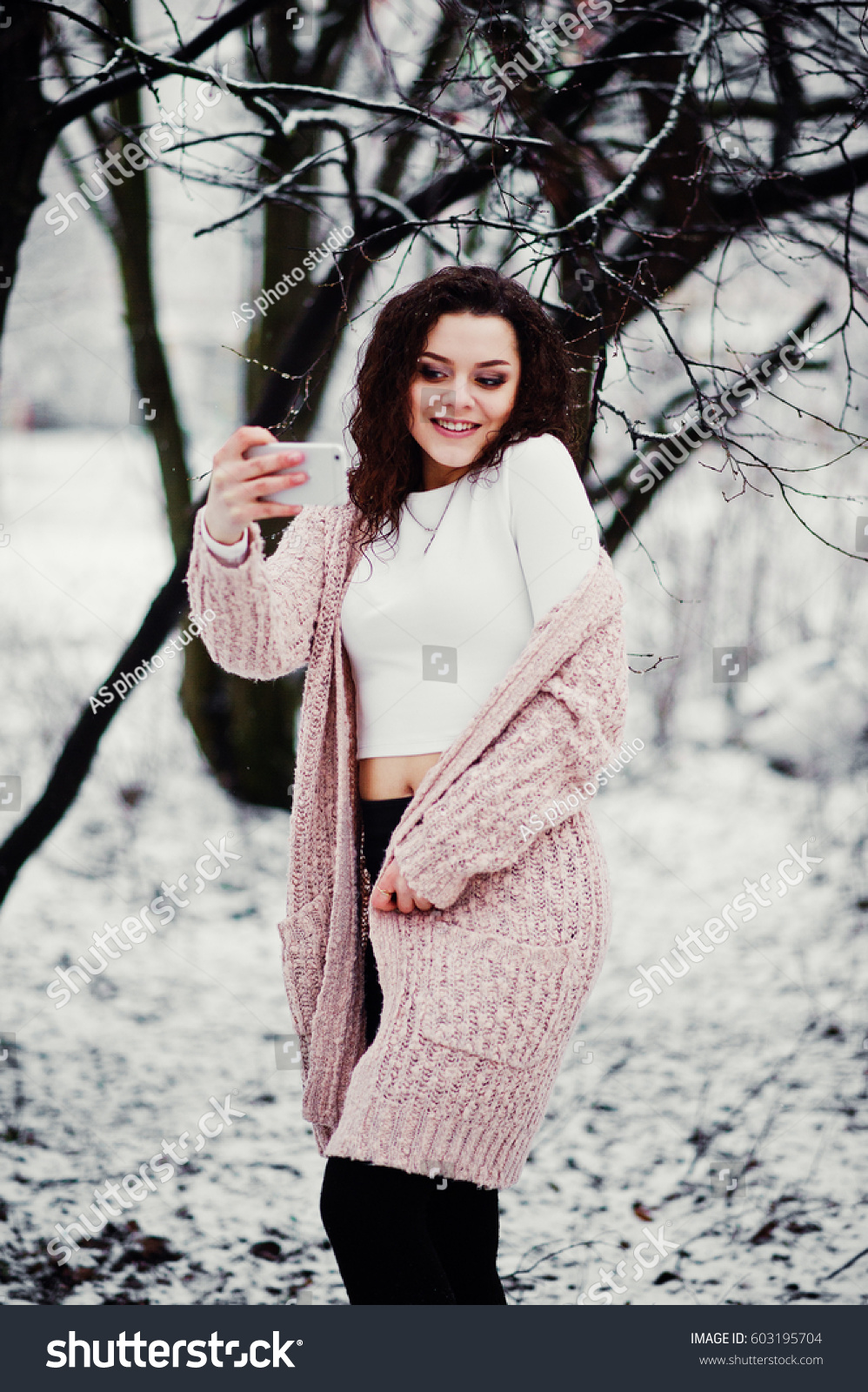 e637cbfac7 Curly brunette girl with mobile phone at hand making selfie background  falling snow