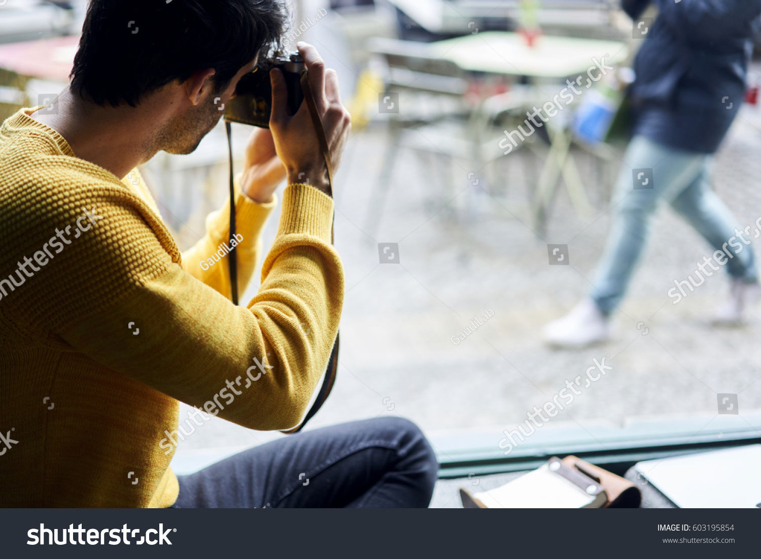 Back view of male photographer amateur taking pictures of strangers  strolling city streets capture characters while
