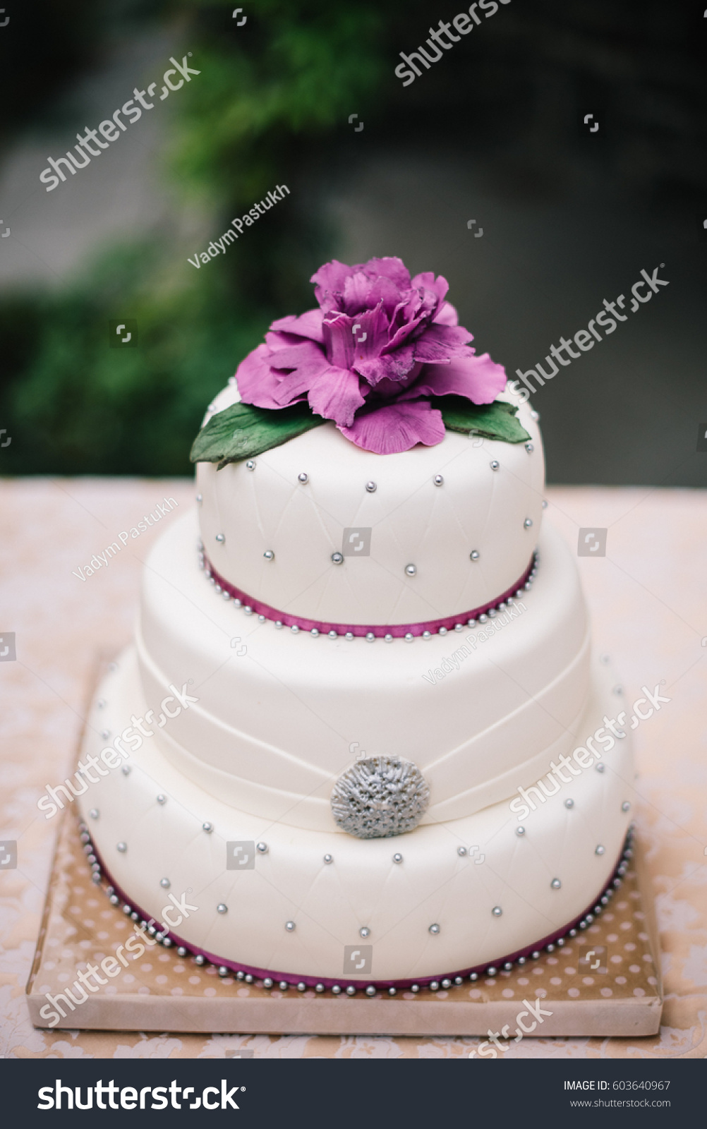 Three Layered Wedding Cake Covered With White Fondant Decorated