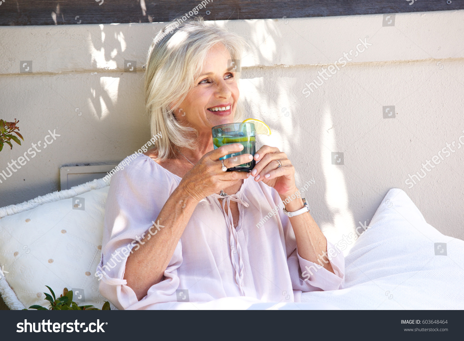 portrait relaxed older woman outside drinking stock photo (royalty