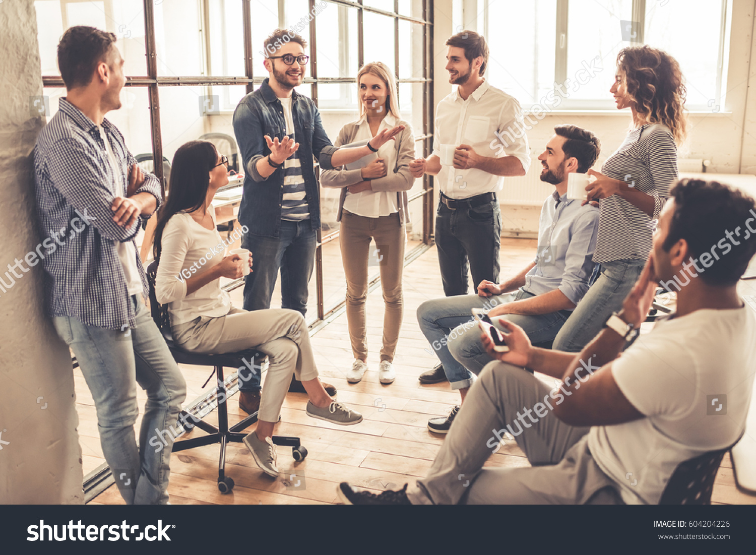Successful young business people are talking and smiling during the coffee break in office