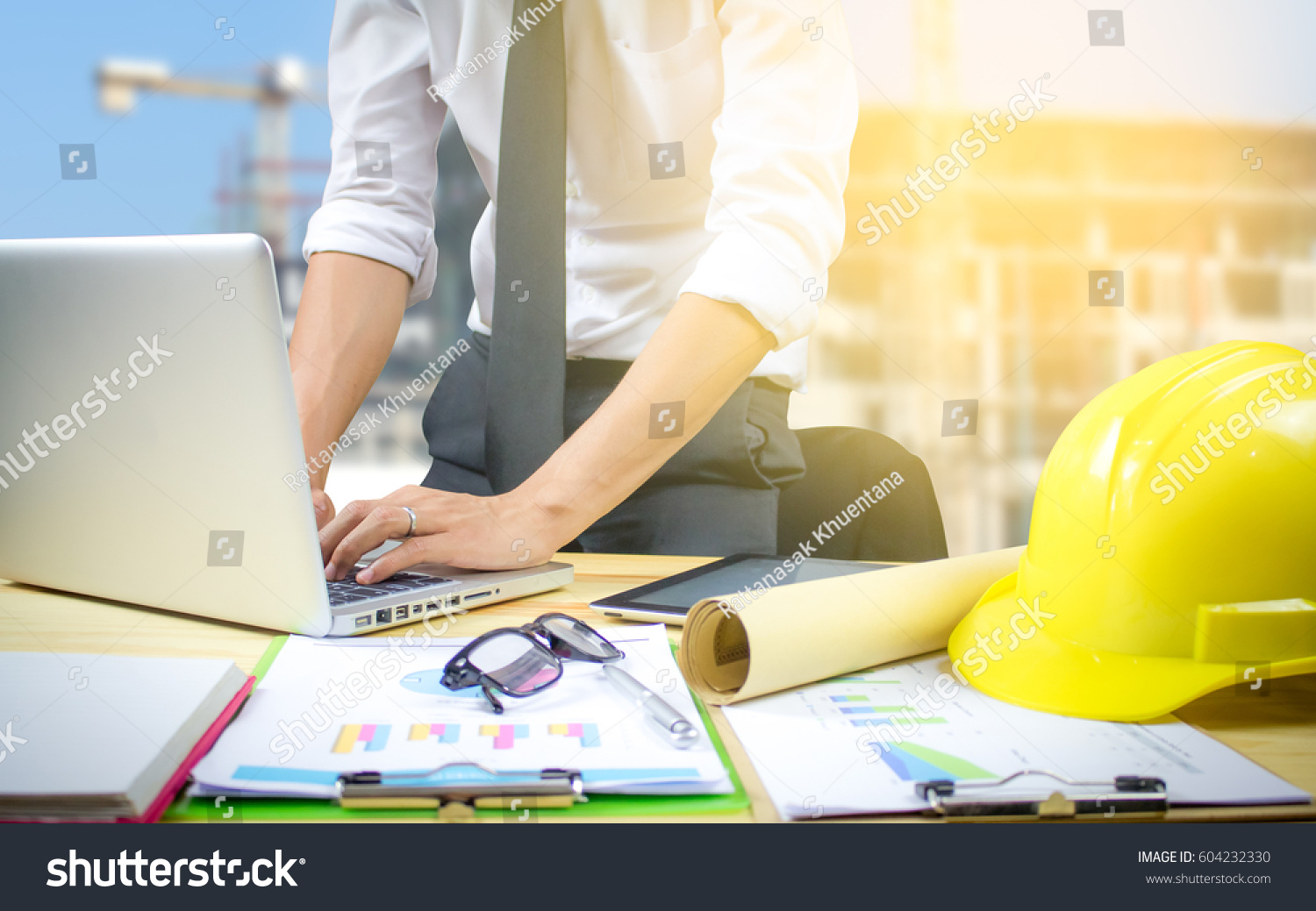 Engineer hold security helmet blueprint paper stock photo royalty engineer hold security helmet and blueprint paper construction drawing plan near laptop computerarchitect working malvernweather Choice Image