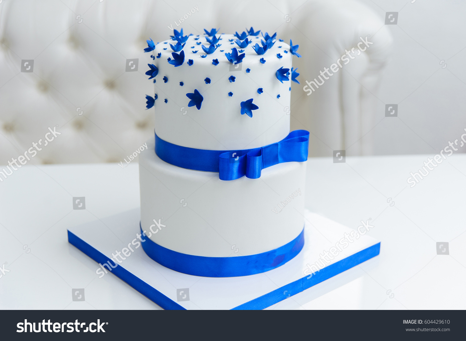 White wedding cake blue flowers bow stock photo royalty free white wedding cake with blue flowers and a bow izmirmasajfo
