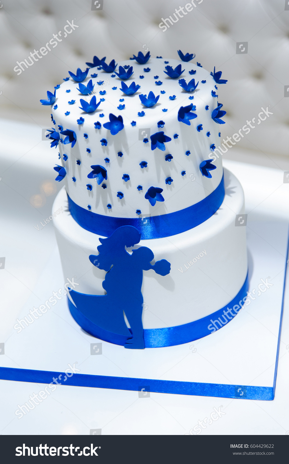 White wedding cake blue flowers bow stock photo royalty free white wedding cake with blue flowers and a bow also with the figures of the izmirmasajfo