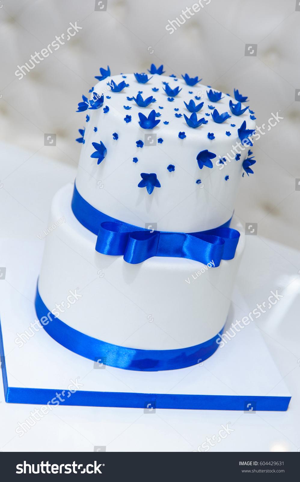 White wedding cake blue flowers bow stock photo edit now 604429631 white wedding cake with blue flowers and a bow izmirmasajfo