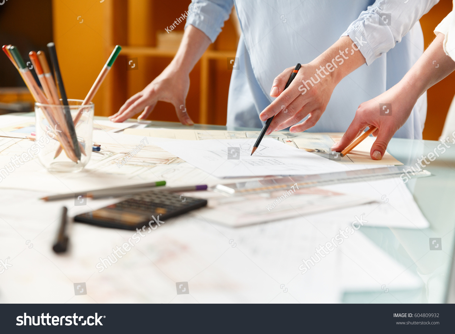 interior designers working on hand drawings of interior at work place