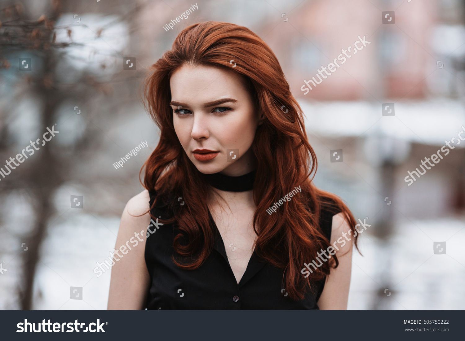 Portrait of glamorous girl with long red hair in black clothes. Woman in  black dress