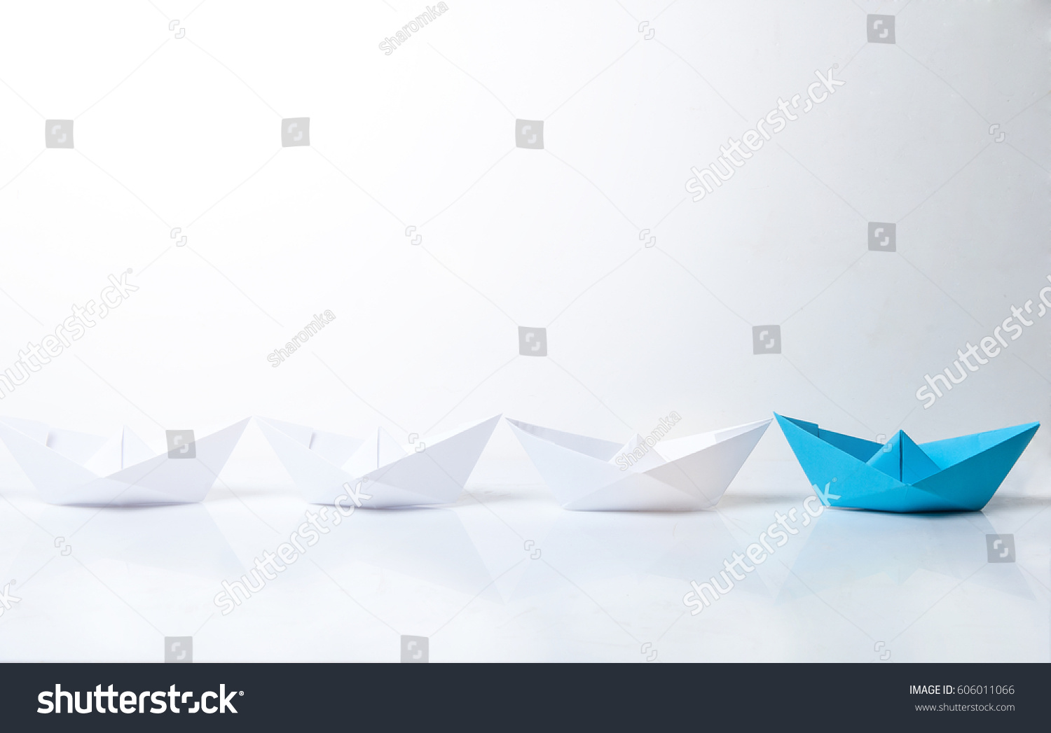 Leadership concept. Blue paper boat leading among white ships. Set of origami boats. Winner red paper ship on white background #606011066
