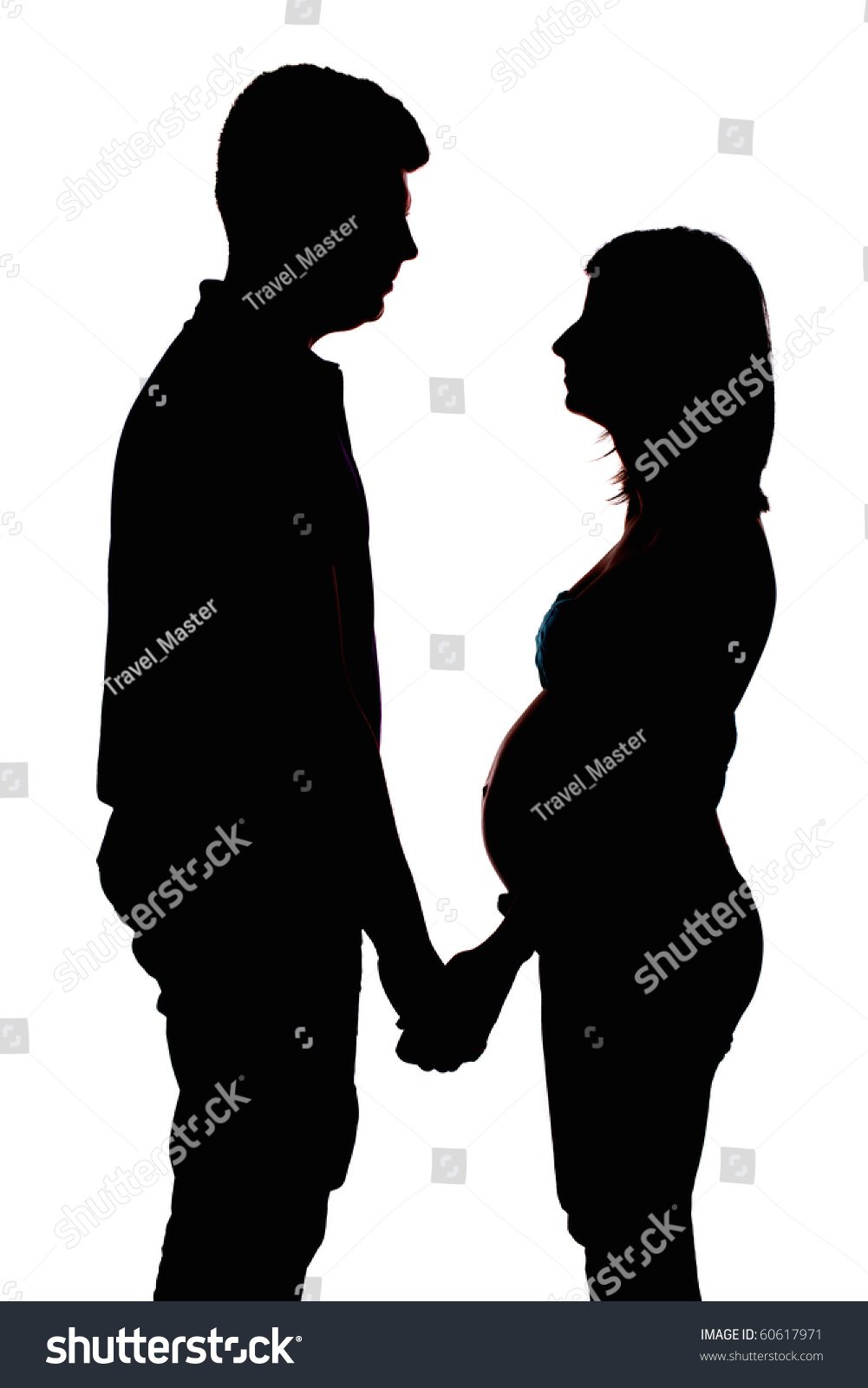 soft silhouette of couple holding hands expecting baby