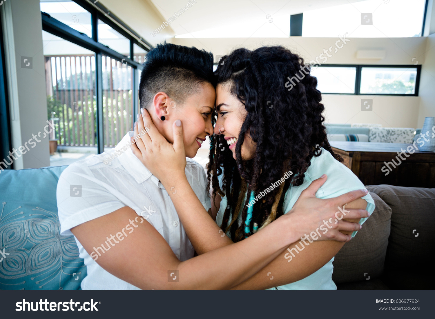 Lesbian couple embracing each other on sofa in living room