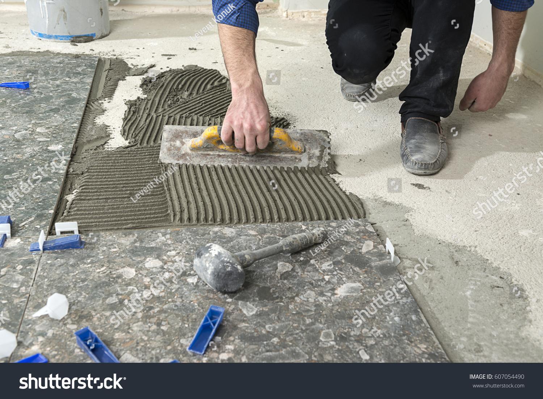 Handyman applying cement adhesive ceramic tile stock photo handyman applying cement adhesive for ceramic tile on floor dailygadgetfo Gallery