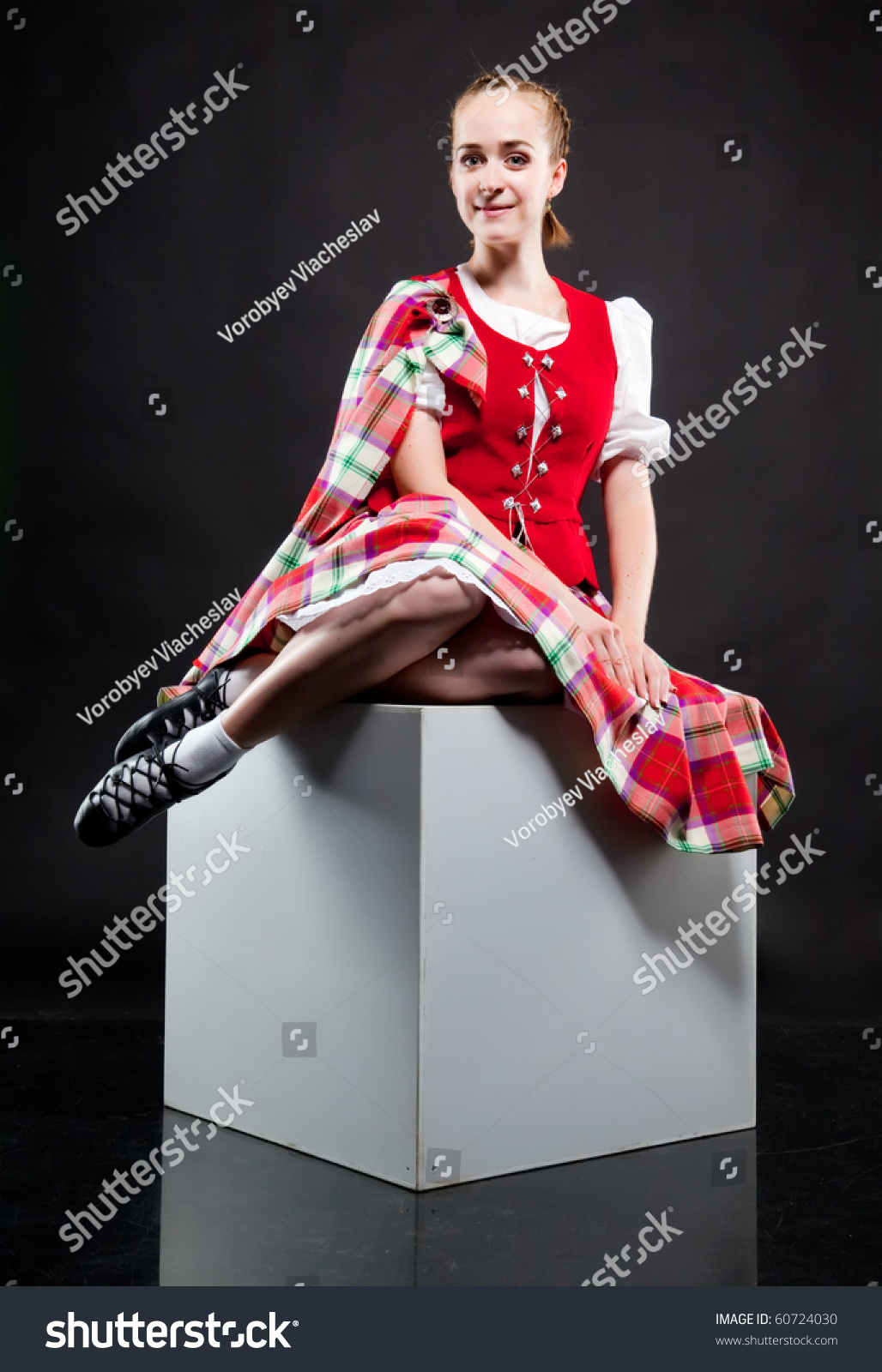 The girl dancing the Scottish dance in a kilt sitting on a white cube