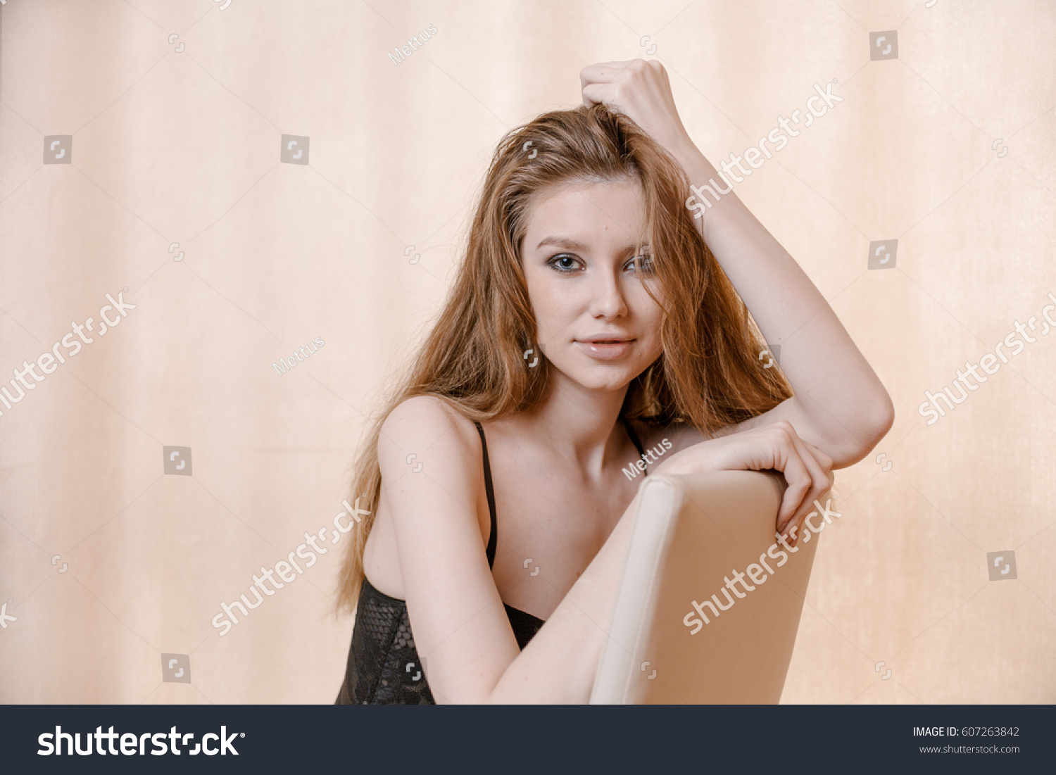 Blond haired woman in pensive state posing on chair with copyspace.